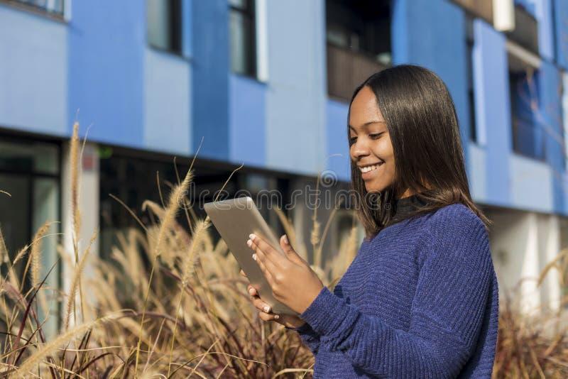 Vista lateral de una situación afroamericana de la muchacha, mientras que sostiene la tableta en sus manos y miradas en ella fotos de archivo