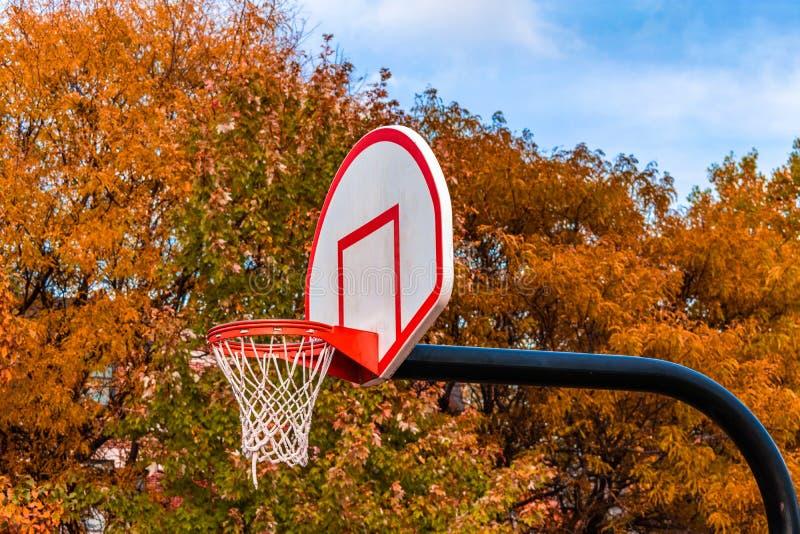 Vista lateral del aro de baloncesto con Autumn Colored Trees en el fondo imagen de archivo