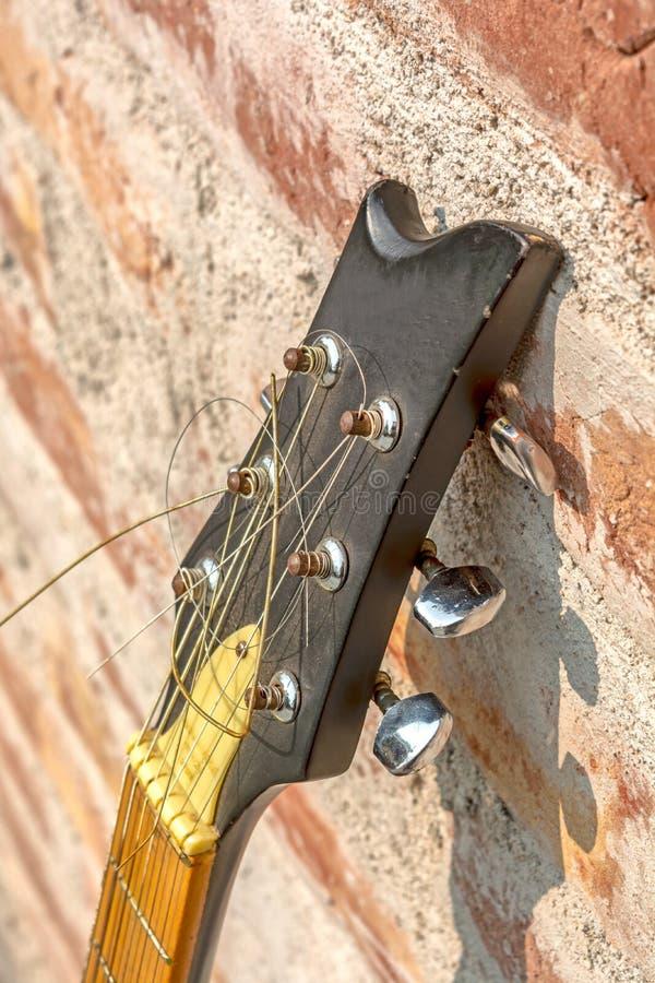 Vista lateral del cabezal de la guitarra acústica de la Seis-secuencia en fondo de la pared imagen de archivo libre de regalías
