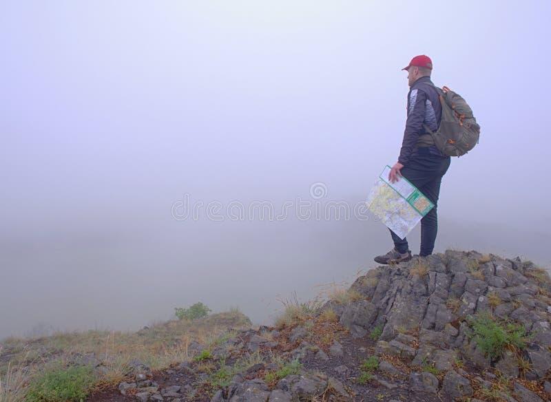 Vista lateral del caminante con la carta de la lectura de la mochila imágenes de archivo libres de regalías