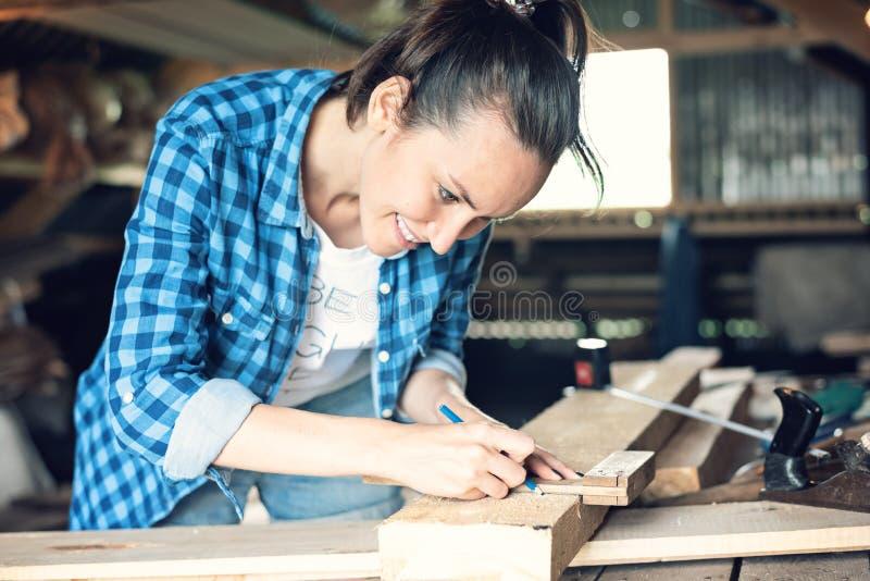 Vista lateral del carpintero de sexo femenino sonriente a marcar en un corte de la sierra de la banda del lápiz del tablero de ma imagen de archivo libre de regalías