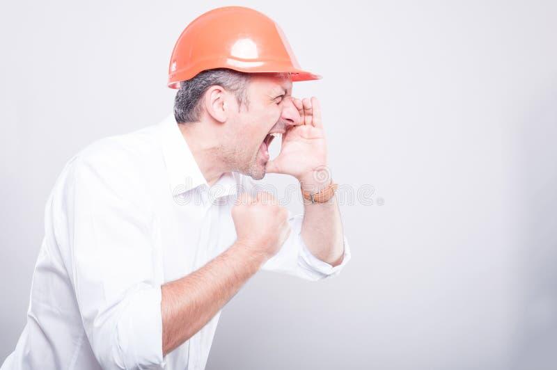 Vista lateral del casco de protección que lleva del arquitecto que grita hacia fuera ruidosamente fotografía de archivo libre de regalías