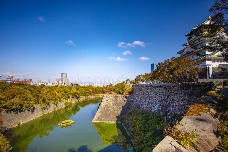 Vista lateral del castillo de Osaka y del horizonte urbano contra el cielo azul claro hermoso imágenes de archivo libres de regalías