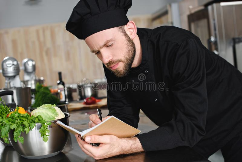 vista lateral del cocinero hermoso que anota nueva receta al cuaderno foto de archivo