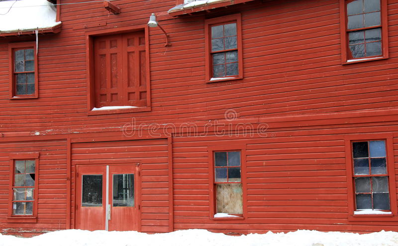 Vista lateral del granero rojo rústico en día nevoso fotografía de archivo libre de regalías