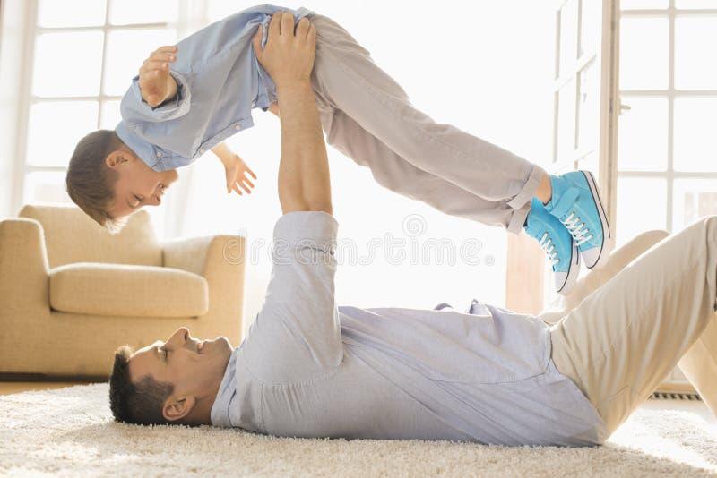 Vista lateral del hijo de elevación del padre juguetón mientras que miente en piso en casa foto de archivo