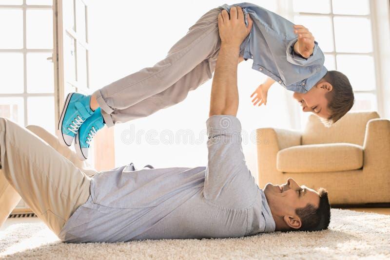 Vista lateral del hijo de elevación del padre juguetón mientras que miente en piso en casa fotografía de archivo
