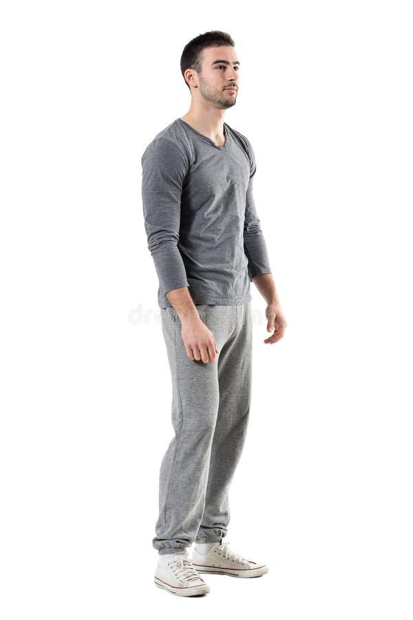 Vista lateral del hombre atlético deportivo joven en sweatpants y de la camiseta que mira lejos foto de archivo libre de regalías