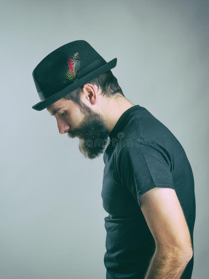 Vista lateral del hombre barbudo hunched triste con el sombrero que mira abajo imagen de archivo libre de regalías