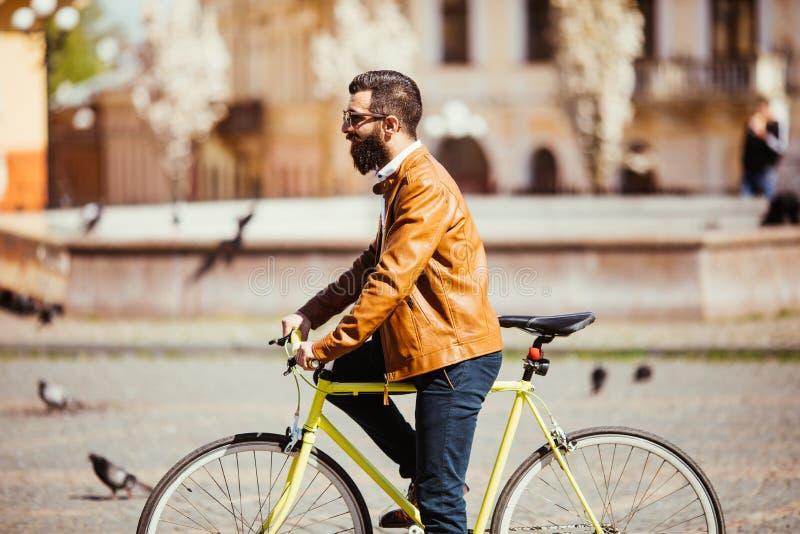 Vista lateral del hombre barbudo joven hermoso en las gafas de sol que parecen ausentes mientras que monta en su bicicleta al air imagen de archivo