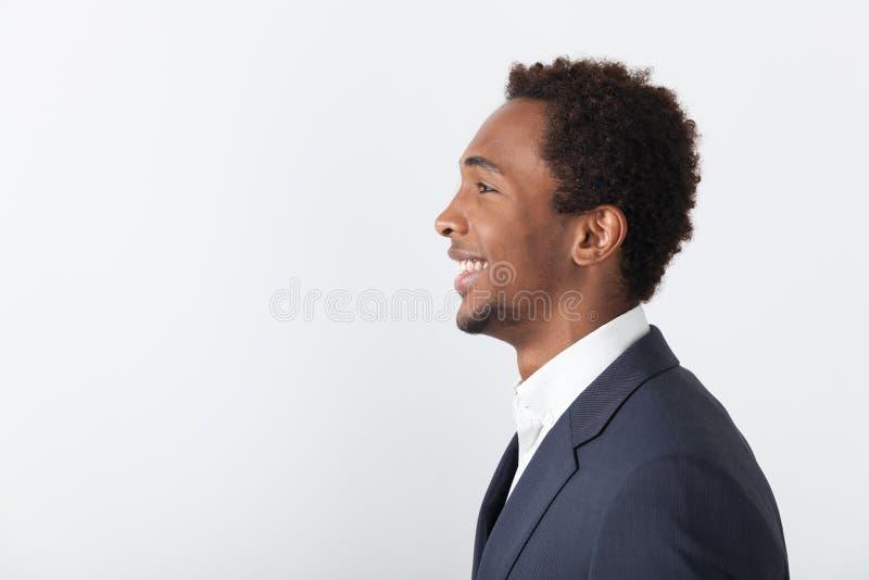 Vista lateral del hombre de negocios africano sonriente imagen de archivo