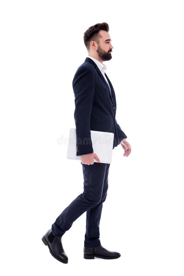 Vista lateral del hombre de negocios barbudo hermoso joven con caminar del ordenador portátil aislado en blanco imagenes de archivo