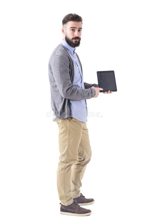 Vista lateral del hombre de negocios barbudo joven que muestra y que señala en la pantalla en blanco de la tableta imagen de archivo