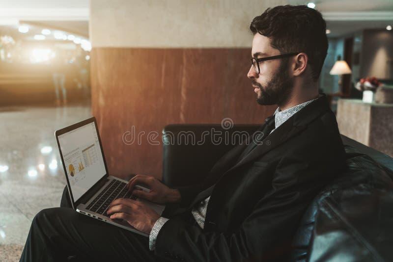 Vista lateral del hombre de negocios con el ordenador portátil en el sofá fotos de archivo