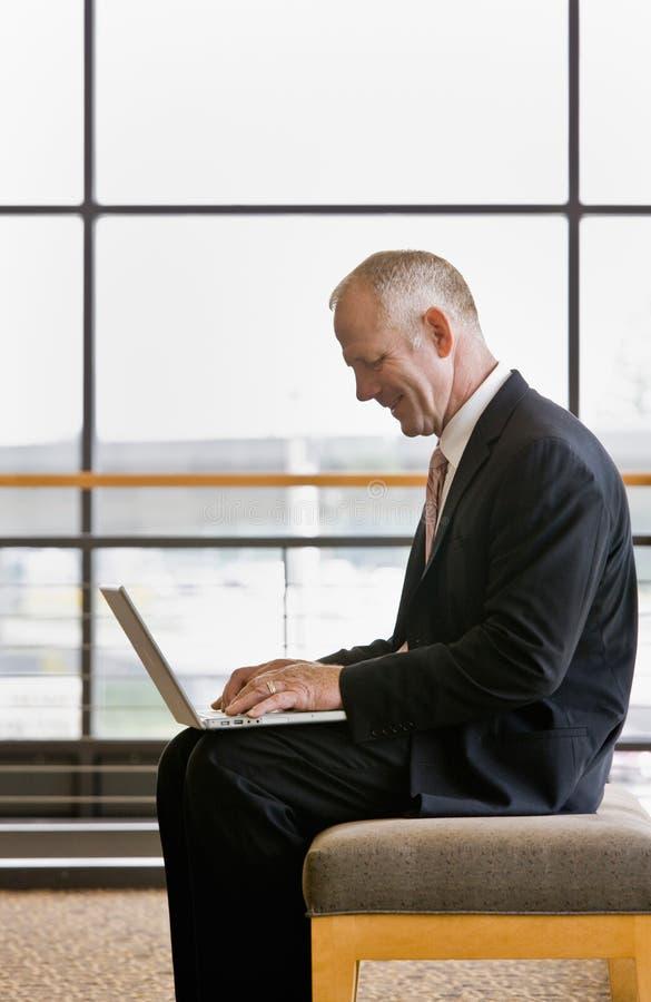 Vista lateral del hombre de negocios maduro que trabaja en la computadora portátil fotografía de archivo