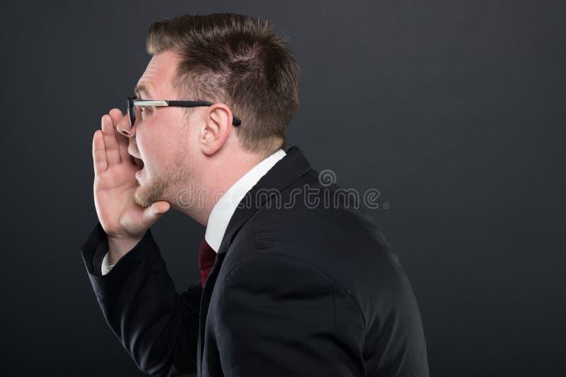 Vista lateral del hombre de negocios que grita hacia fuera ruidosamente fotos de archivo libres de regalías