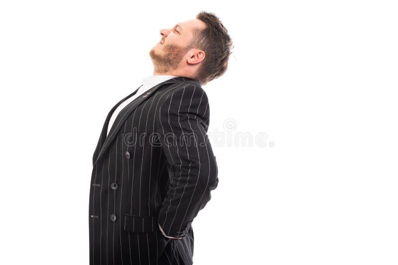 Vista lateral del hombre de negocios que muestra gesto del dolor de espalda fotos de archivo libres de regalías