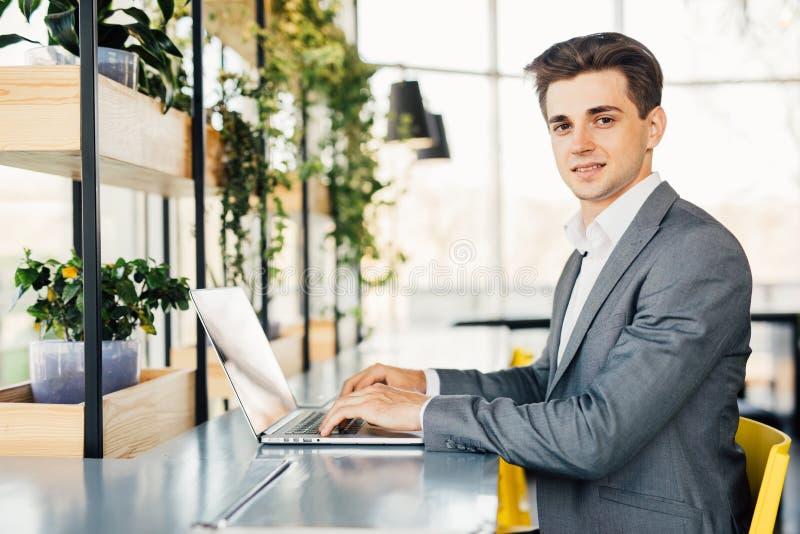 Vista lateral del hombre de negocios que se sienta por la tabla con el ordenador portátil y que mira la cámara fotos de archivo libres de regalías