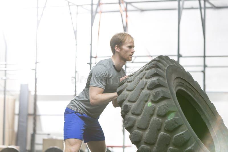 Vista lateral del hombre dedicado que mueve de un tirón el neumático en gimnasio del crossfit foto de archivo