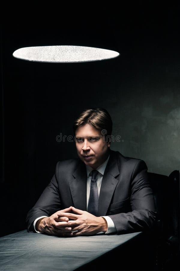 Vista lateral del hombre en el sitio oscuro iluminado por la lámpara foto de archivo