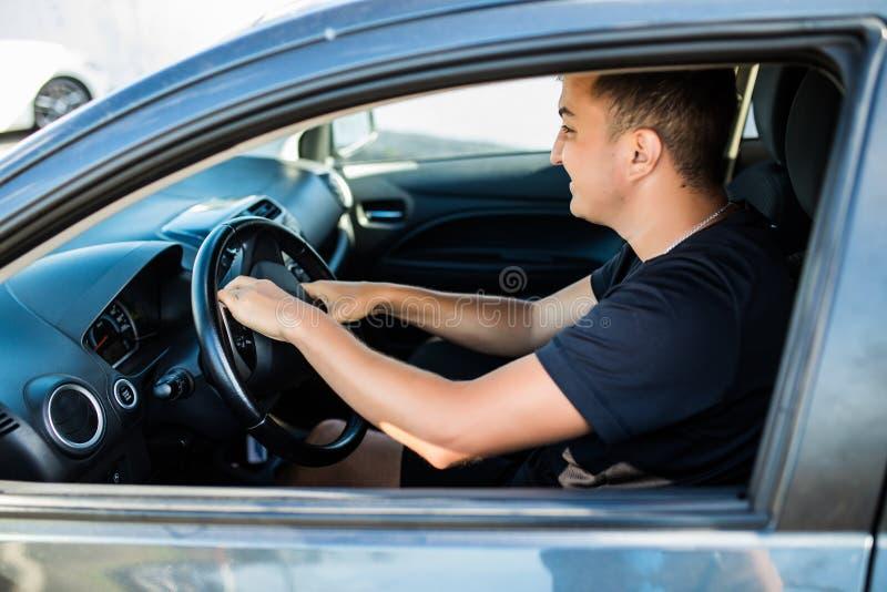 Vista lateral del hombre enojado en el traje que conduce un coche y señales sonoras imagen de archivo