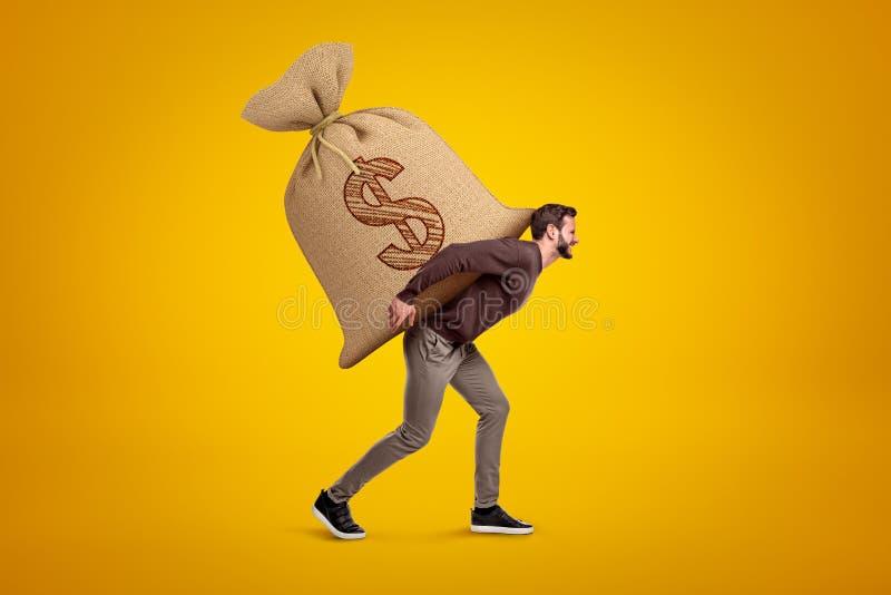 Vista lateral del hombre hermoso joven en la ropa casual que lleva el saco pesado enorme con símbolo del dólar encendido fotografía de archivo