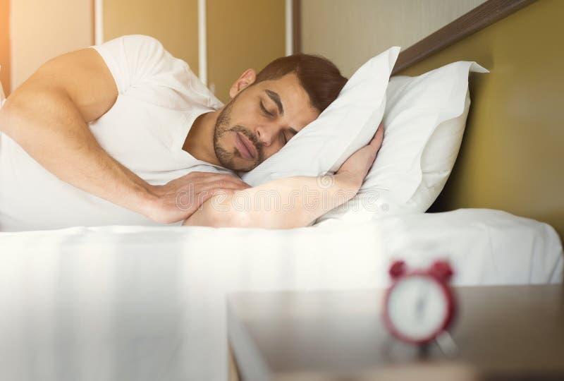 Vista lateral del hombre hermoso que duerme en cama fotos de archivo