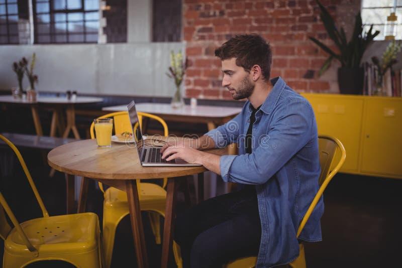 Vista lateral del hombre hermoso que mecanografía en el ordenador portátil mientras que se sienta en la tabla fotos de archivo