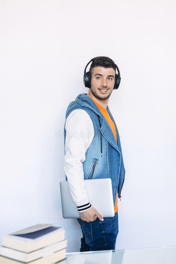 Vista lateral del hombre joven en la ropa casual que se coloca mientras que mira lejos y lleva una PC de la tableta imágenes de archivo libres de regalías