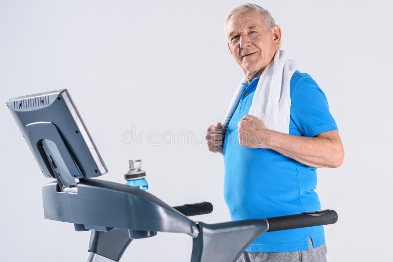 vista lateral del hombre mayor sonriente con la toalla que ejercita en la rueda de ardilla fotos de archivo libres de regalías