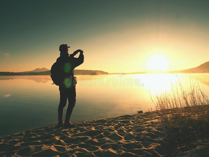 Vista lateral del hombre que toma las fotos de Selfie en la playa Mañana caliente Sun que sube sobre el lago imágenes de archivo libres de regalías