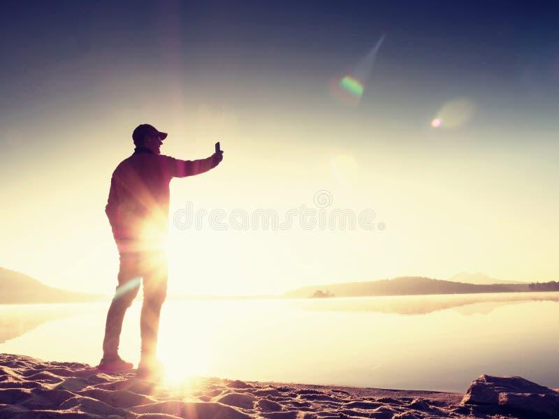 Vista lateral del hombre que toma las fotos de Selfie en la playa Mañana caliente Sun que sube sobre el lago fotos de archivo libres de regalías