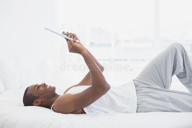 Vista lateral del hombre sonriente del Afro que usa la tableta digital en cama fotos de archivo