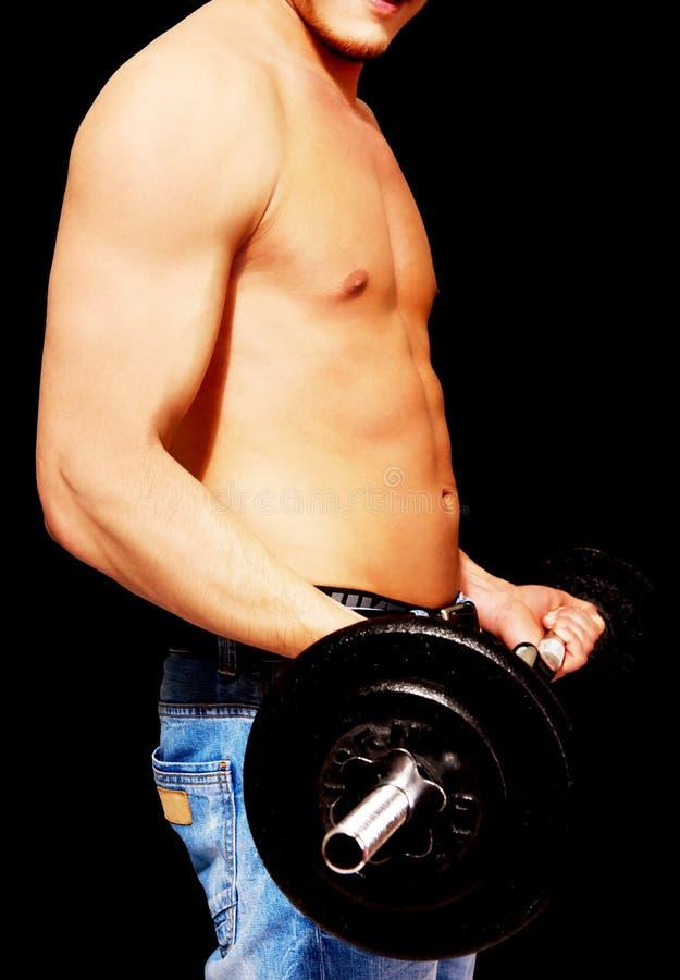 Vista lateral del levantamiento de pesas muscular joven del hombre imagenes de archivo