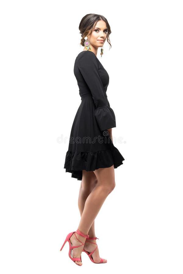 Vista lateral del modelo de moda femenino magnífico en el vestido negro que sonríe en la presentación de la cámara imagenes de archivo