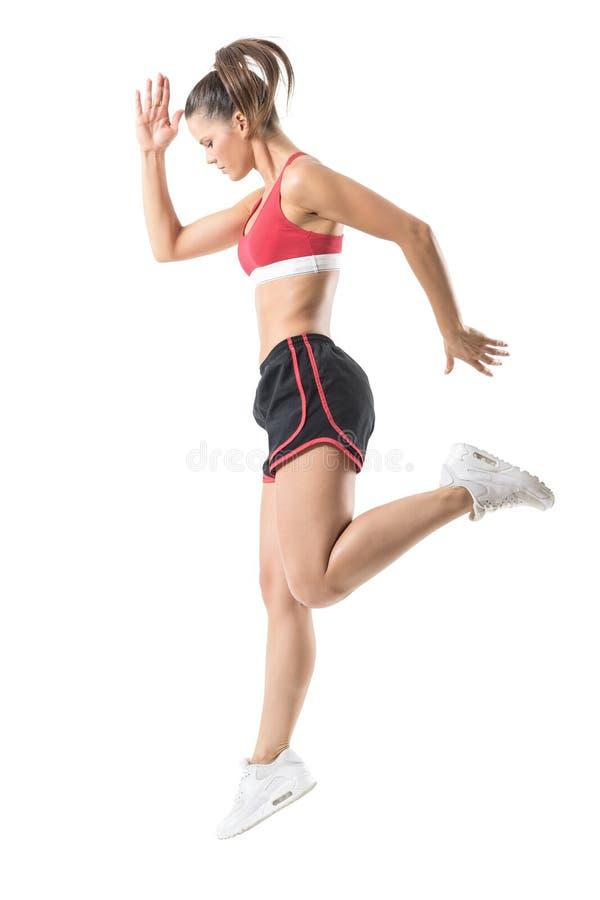 Vista lateral del movimiento de salto enfocado deportivo de la mujer confiada de la aptitud foto de archivo