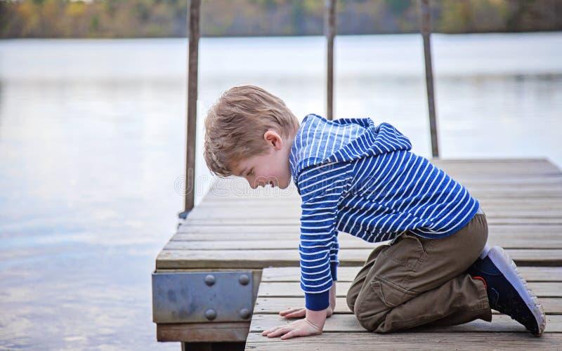 Vista lateral del muchacho en el muelle que mira en el lago foto de archivo