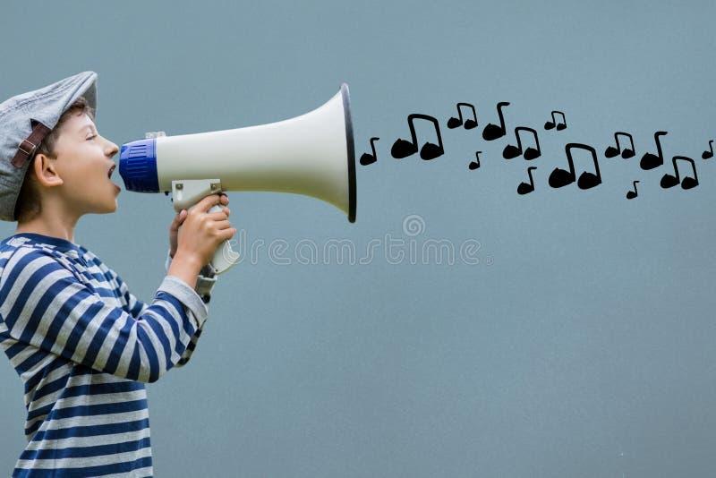 Vista lateral del muchacho que habla en megáfono con las notas musicales que salen foto de archivo