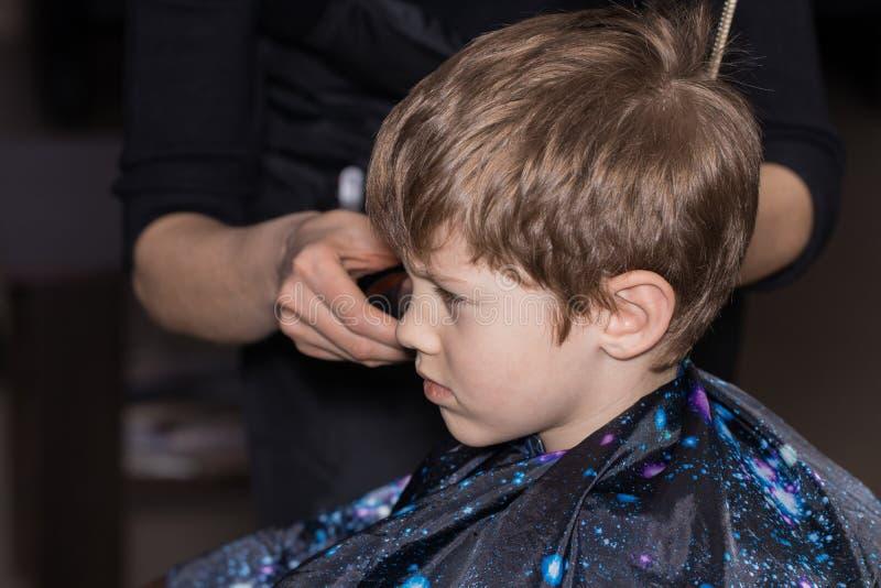 Vista lateral del niño pequeño lindo que consigue corte de pelo del peluquero en t fotografía de archivo libre de regalías