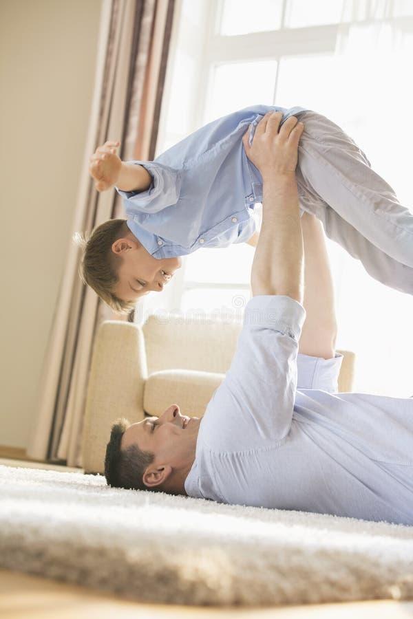 Vista lateral del padre juguetón que coge al hijo mientras que miente en piso en casa fotos de archivo