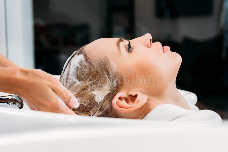 vista lateral del pelo que se lava del peluquero para el cliente imagen de archivo libre de regalías