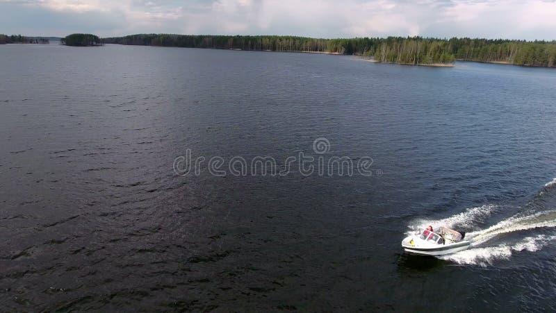 Vista lateral del pequeño montar a caballo del powerboat en el lago grande, visión aérea desde el abejón, copyspace imagen de archivo