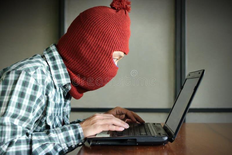 Vista lateral del pirata informático enmascarado que lleva un pasamontañas que mira un ordenador portátil y que roba datos de la  fotografía de archivo