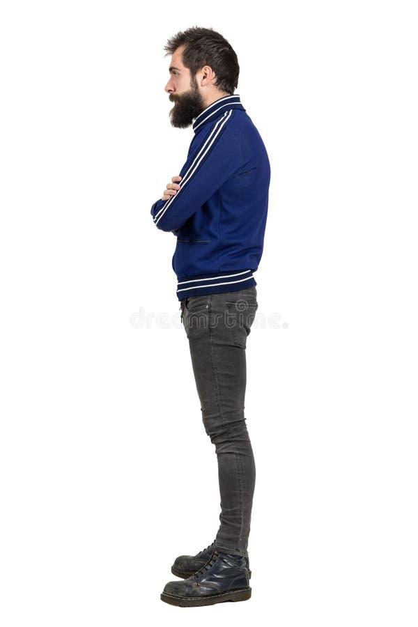Vista lateral del punker barbudo joven en la chaqueta azul del chándal que mira lejos con los brazos cruzados imagenes de archivo