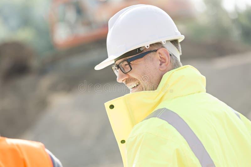 Vista lateral del supervisor de sexo masculino feliz en el emplazamiento de la obra imágenes de archivo libres de regalías