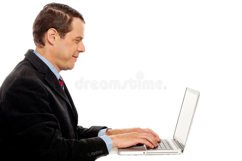 Vista lateral del varón corporativo que pulsa en la computadora portátil fotos de archivo