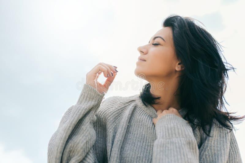 Vista lateral del viajero caucásico moreno de la mujer joven con el pelo ventoso, soñando contra el cielo de la luz del sol Hembr imagen de archivo libre de regalías