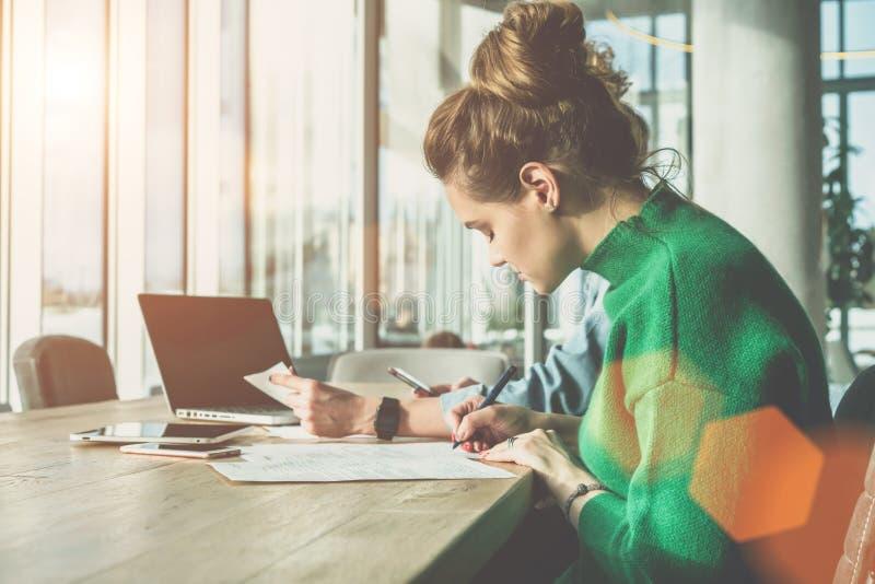 Vista lateral, dia ensolarado, duas mulheres de negócio novas que sentam-se na mesa no escritório Primeira mulher para assinar or imagem de stock