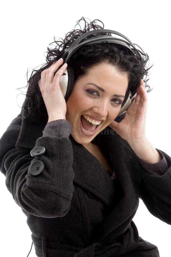 Vista lateral do auscultadores desgastando de sorriso da mulher fotos de stock royalty free