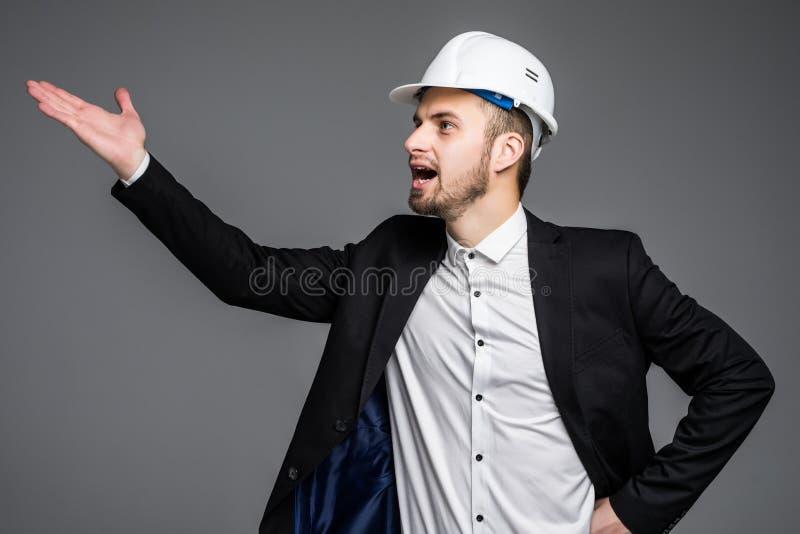 Vista lateral do capacete de segurança vestindo do arquiteto que grita para fora ruidosamente no fundo cinzento com espaço do tex fotografia de stock royalty free